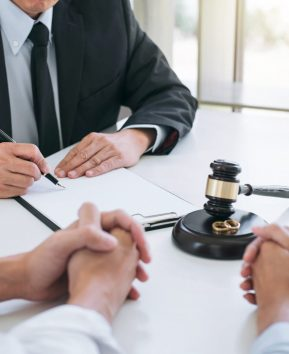 Agreement prepared by lawyer signing decree of divorce (dissolution or cancellation) of marriage, husband and wife during divorce process with male lawyer or counselor and signing of divorce contract.